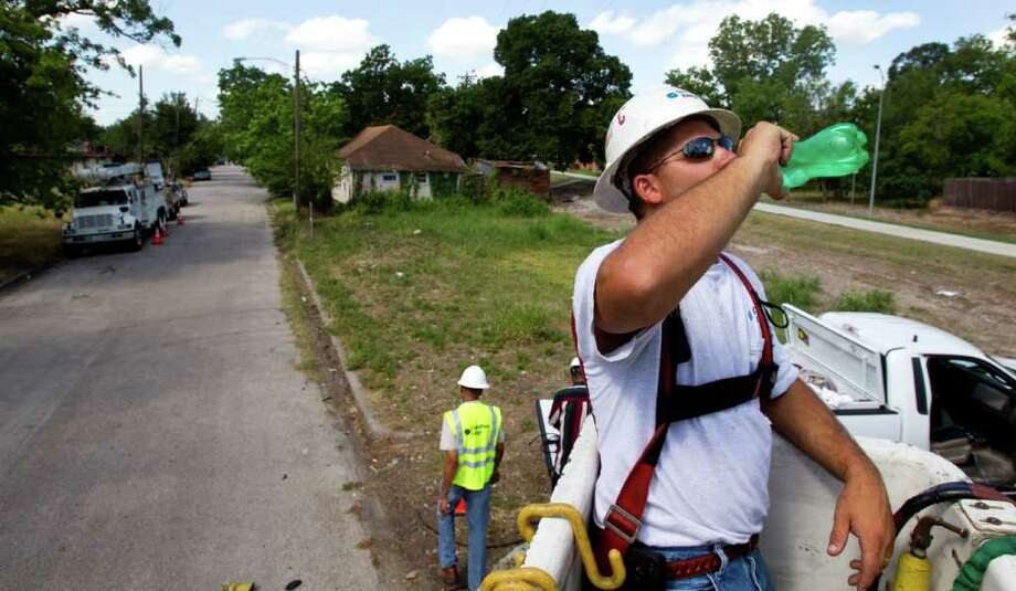 Allen Chelette takes a drink of water while working in Third Ward Wednesday, June 29, 2011, in Houston. OSHA is reminding employers that they have to provide their workers with protection from the heat. Centerpoint Energy has its linemen and other folks who work outside every day drink fluid every 15 to 20 minutes so they consume a quart an hour of either water or Gaterode.( Brett Coomer / Houston Chronicle ) Photo: Brett Coomer, Staff / © 2011 Houston Chronicle