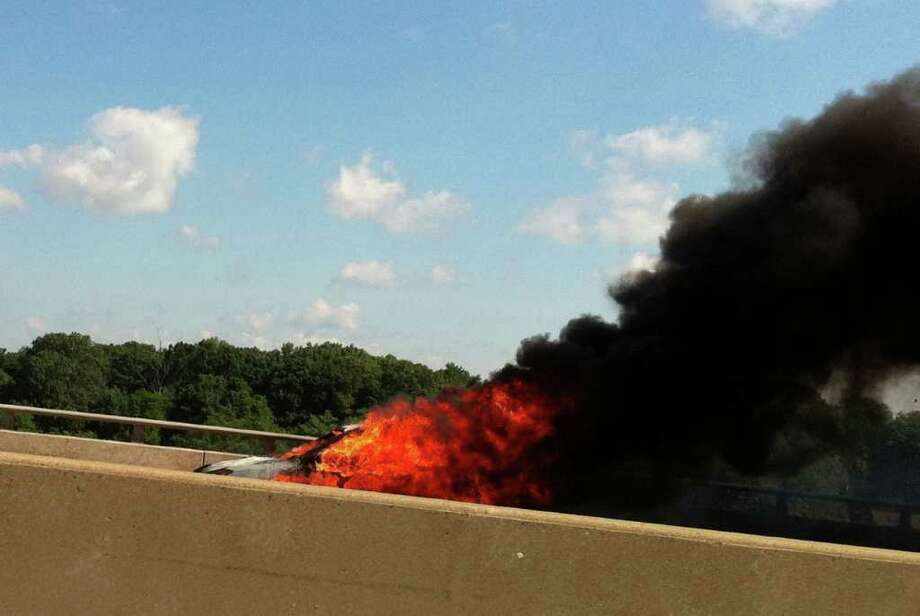 A car is fully engulfed in flames on I-95 southbound in between exits 18 and 17 in Westport, Conn. on Thursday, June 30, 2011. Photo: Brittany Lyte / Connecticut Post