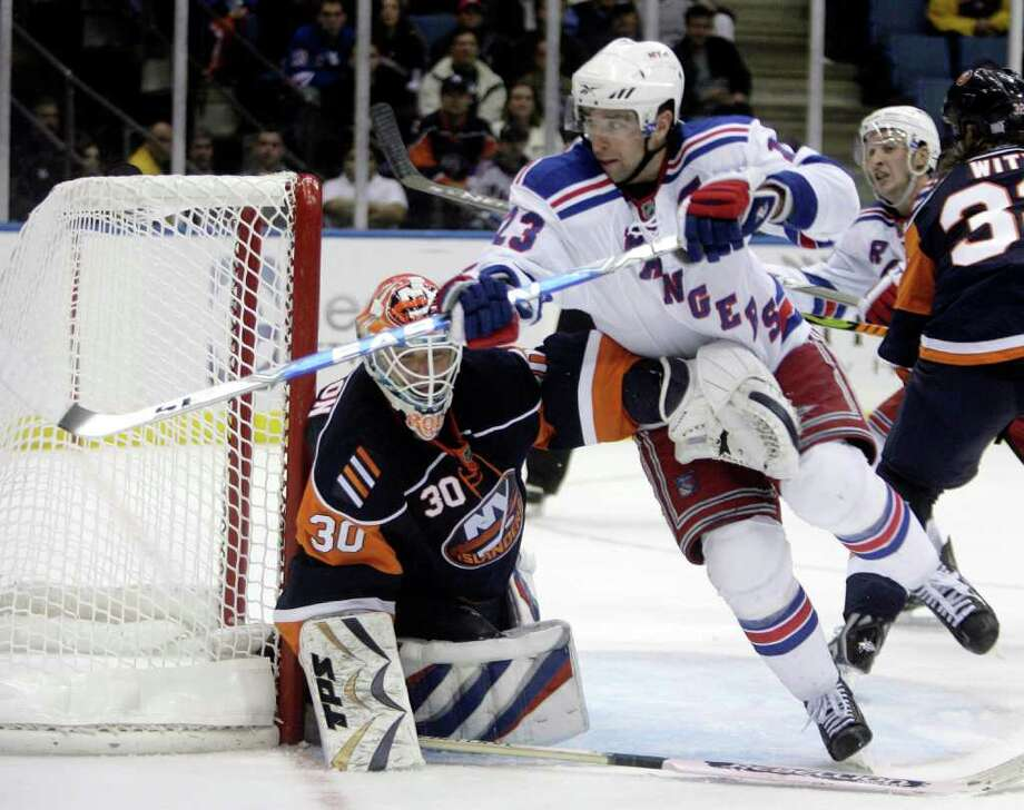 New York Islanders goalie Dwayne Roloson, left, keeps an arm on New York Rangers' Chris Drury during the third period of the NHL hockey game Wednesday, Oct. 28, 2009, in Uniondale, N.Y.   The Islanders beat the Rangers, 3-1. Photo: AP Photo/Seth Wenig / Connecticut Post Contributed
