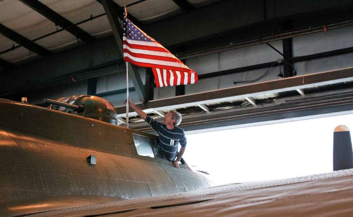 Alan Peover mounts an American flag atop the B-17 on June 30, 2011, before its move from a hangar at Boeing Field, in Seattle, to the Museum of Flight.