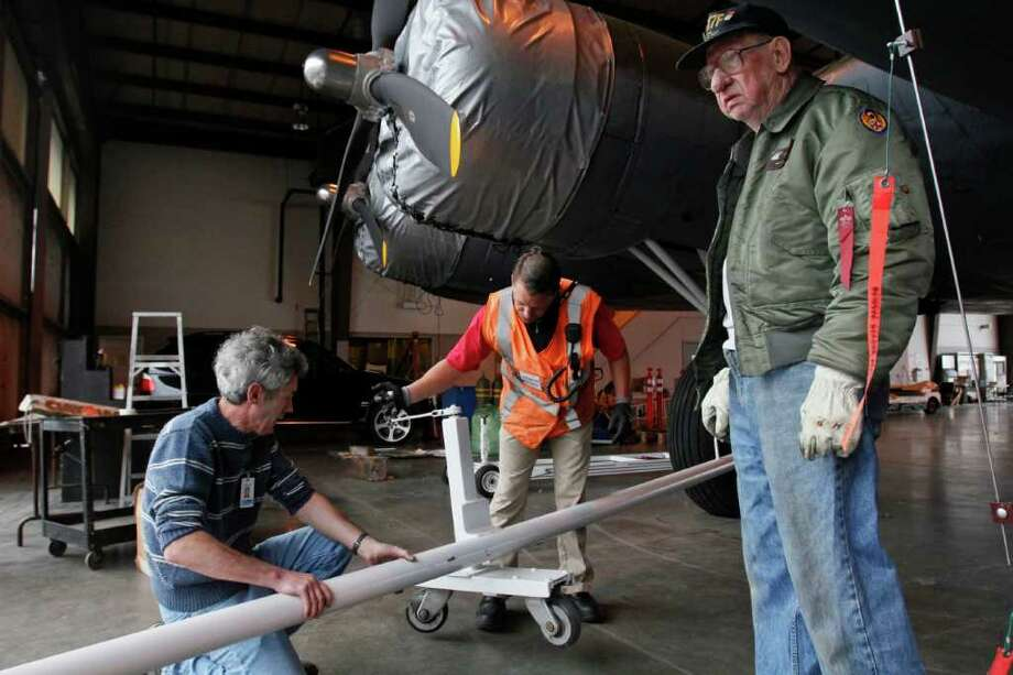 (From left) Alan Peover, Tracy Moore, and Herb Phelan attach a towing mechanism to  the newly restored B-17 on Thursday, June 30., 2011 at Boeing Field, in Seattle. Photo: JOE DYER / SEATTLEPI.COM