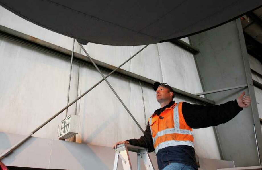 A helper assures that the B-17's massive wings will clear the walls of the hangar as it is backed out to be moved to the Museum of Flight on Thursday, June 30, 2011 in Seattle. Photo: JOE DYER / SEATTLEPI.COM