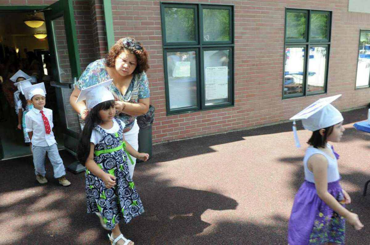 Greenwich Head Start First Steps teacher Lily Herrera fixes Emily Melendez's capbefore the Greenwich Head Start graduation ceremony at Family Centers in Armstrong Court on Thursday, June 30, 2011.