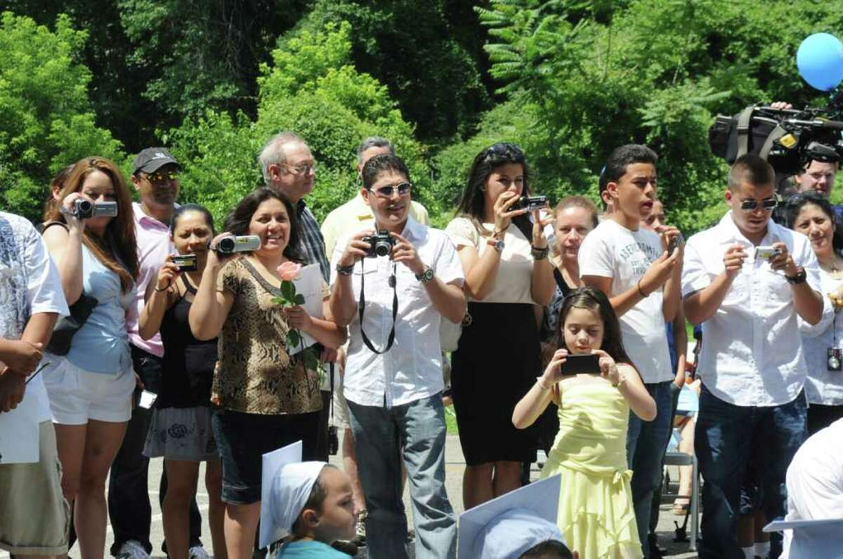 Parents and friends takes photographs at the Family Centers' Greenwich Head Start graduation ceremony to celebrate 32 students moving on to kindergarten at Armstrong Court on Thursday, June 30, 2011.