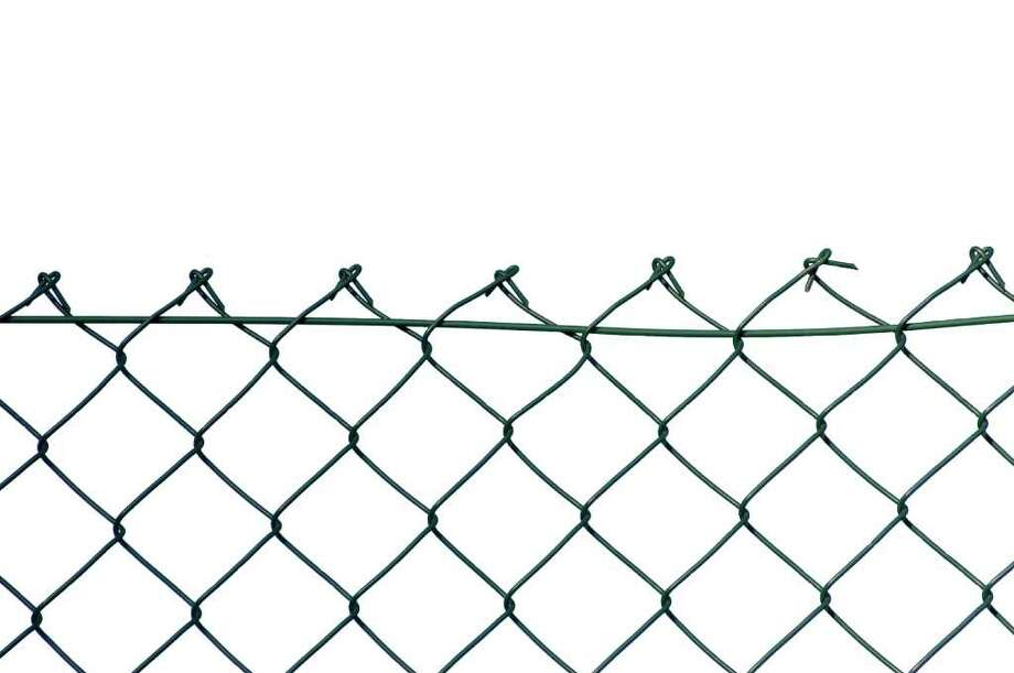 If a neighbor hangs ladders from your fence or rests things against it, that might all be considered trespassing, especially if the fence is just inside your property line and doesn't encroach onto his property. Photo: Brilt - Fotolia, Fence