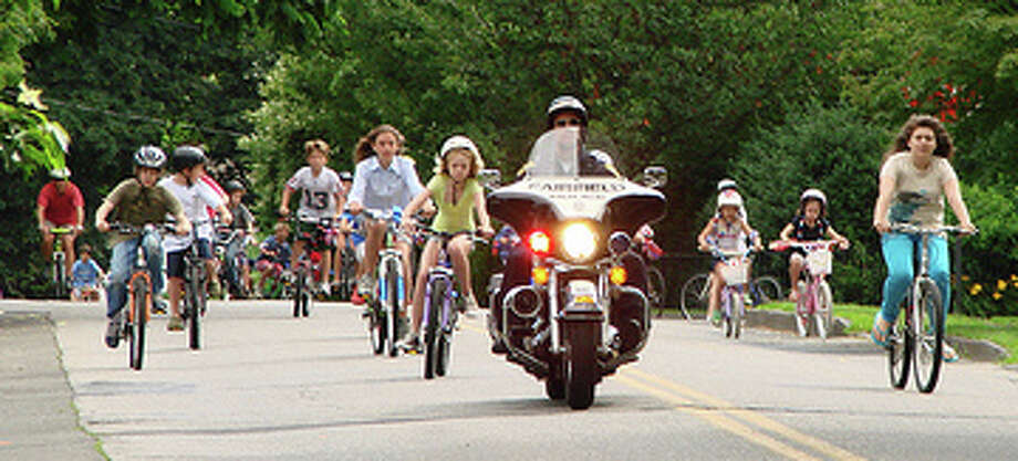 Bikes follow a police escort during Pequot Library's Fourth of July parade. Photo: Contributed Photo