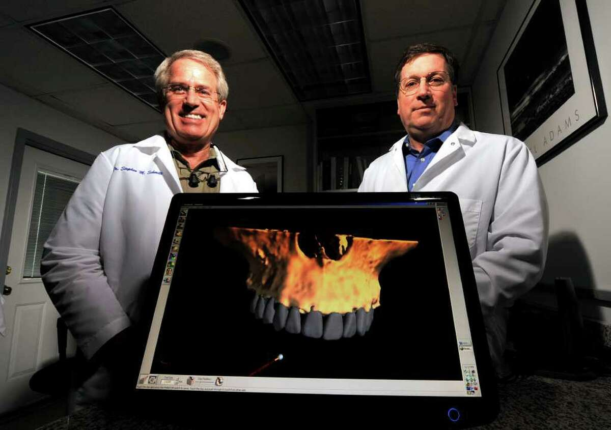 Dentists Dr. Stephen Schmidt (left) and Dr. Benjamin Young use 3D modeling of patients mouths to produce dentures and implants at NeXsmile.