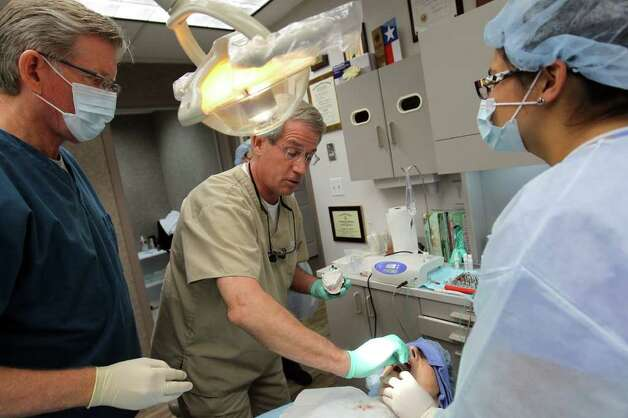 Dr. Jack Shirley, left, and Dr. Steve Schmitt place implant screws for a patient's lower jaw during a process of computer aided dental implants at the NexSmile offices. Photo: Jennifer Whitney, Special To The Express-News / special to the Express-News