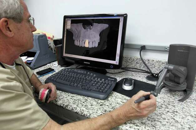 "Dr. Steve Schmitt studies a virtual 3D model of a patient's jaw created from a scan with a device he describes as a ""backwards robotic arm"" that allows him to feel exactly how the teeth fit into the bone structure of the jaw during the process of computer aided dental implants. Photo: Jennifer Whitney, Special To The Express-News / special to the Express-News"
