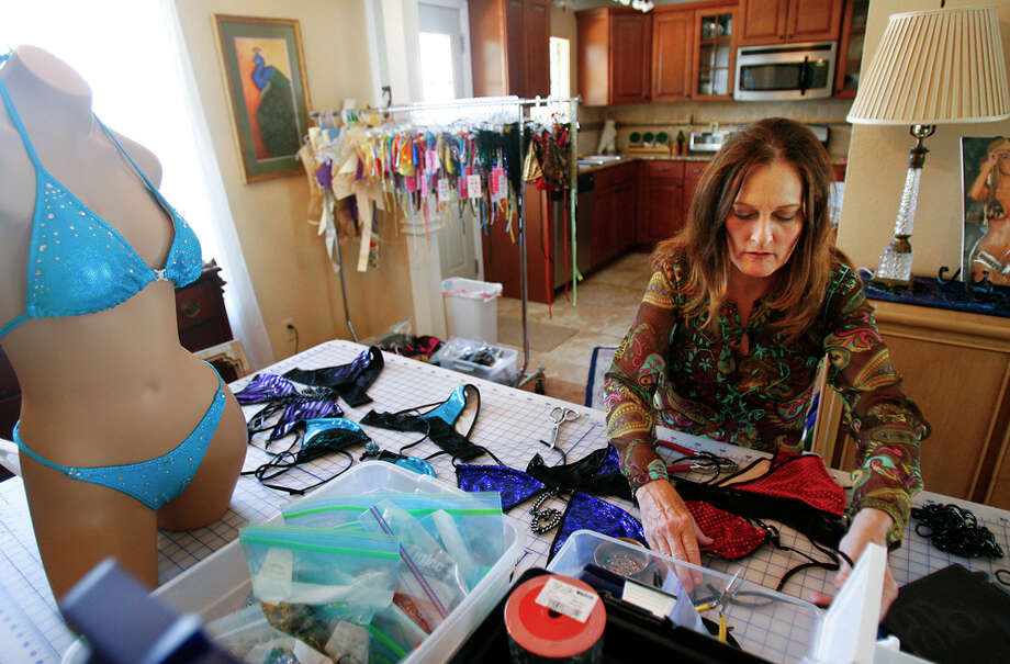 Carrie Harrell adds decorative elements to her Lollie Rocks one-of-a-kind bikinis in her studio on the Northwest Side. She recently made 37 bikinis for the Miss Texas Pageant. SALLY FINNERAN / EXPRESS-NEWS