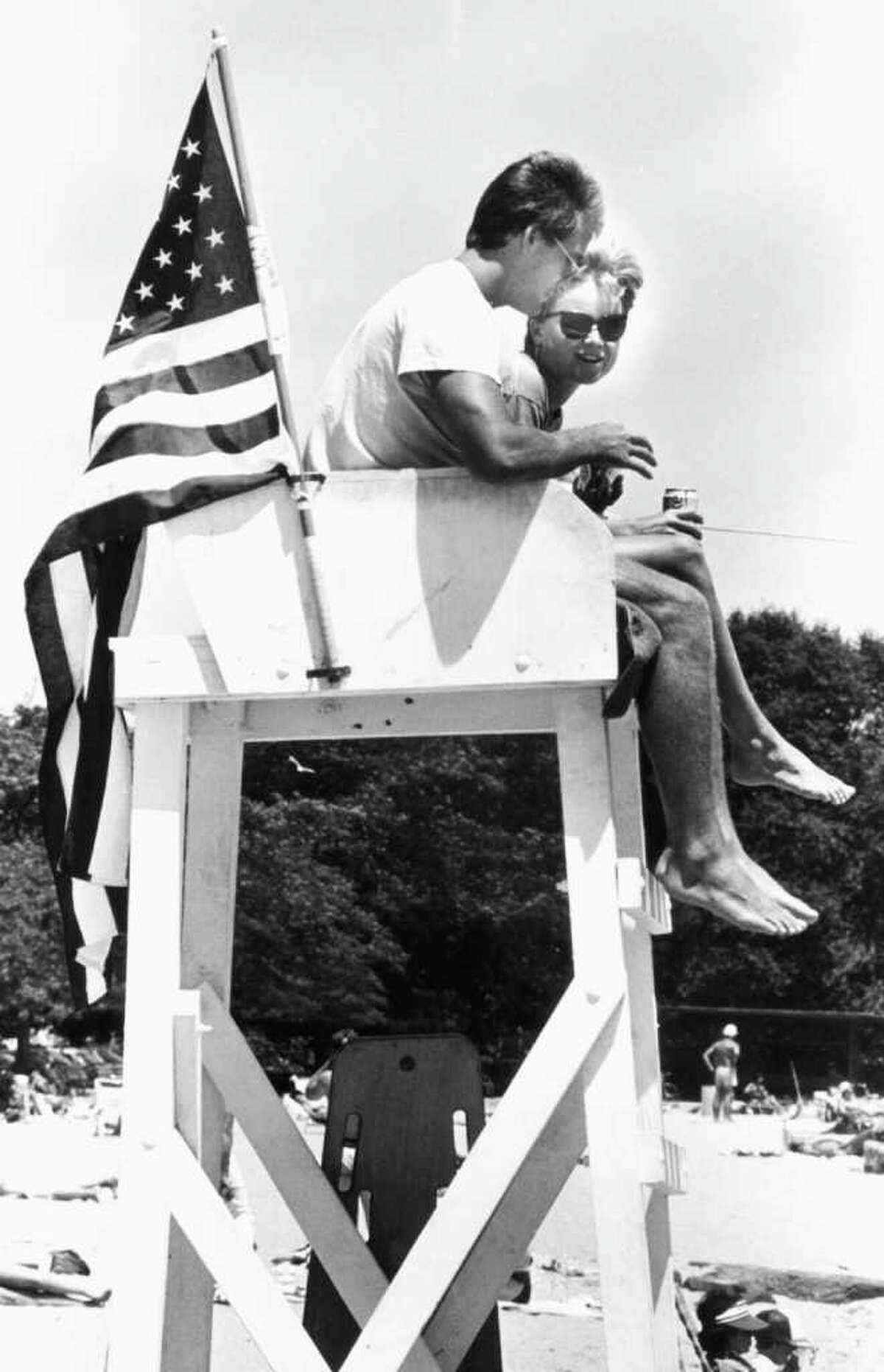 July 4, 1986: Doug Sciullo and Patty Denham, lifeguards at Cummings Park Beach, celebrate the day with Old Glory on their chair.