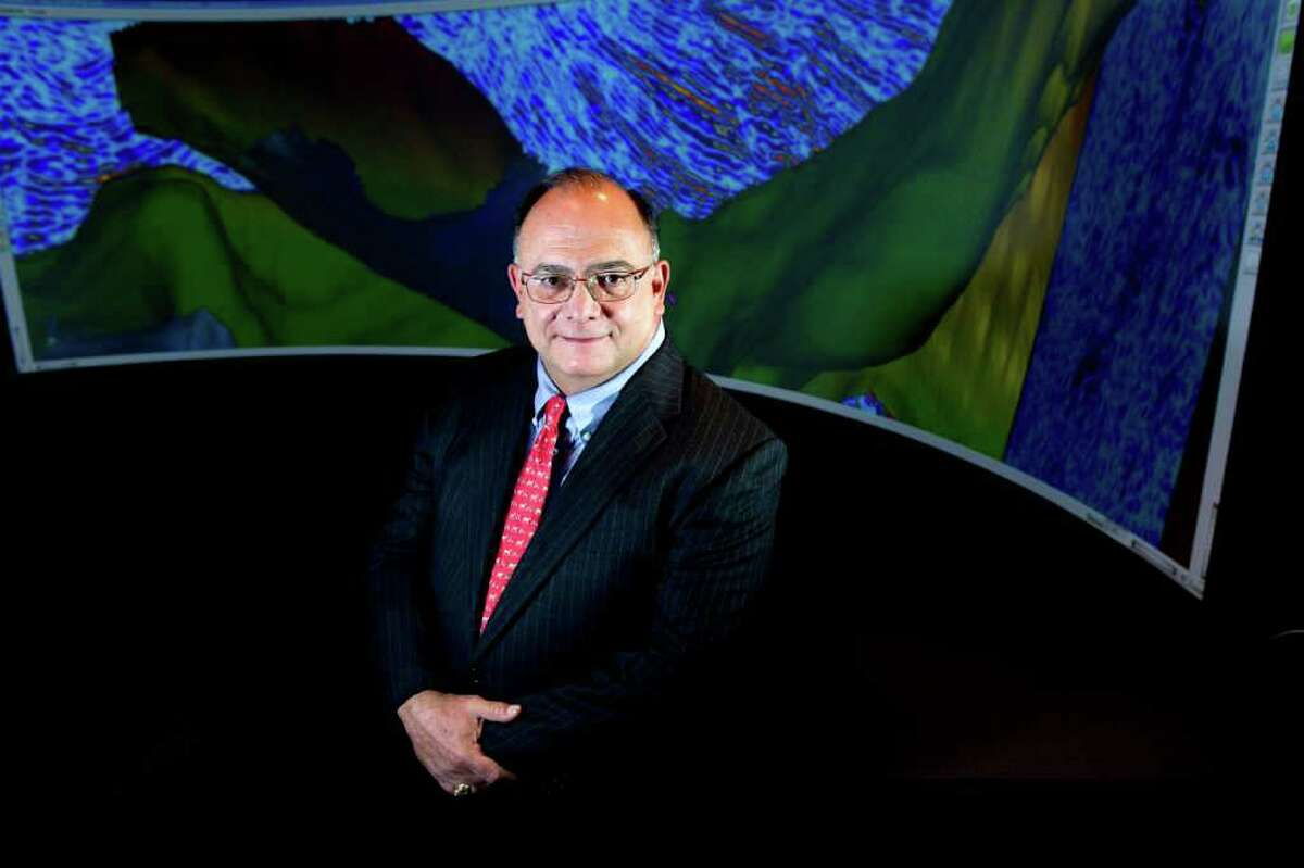 Marathon Oil CEO Clarence Cazalot poses for a portrait in front of seismic date projected in Visionarium at Marathon Oil headquarters Monday, June 20, 2011, in Houston.
