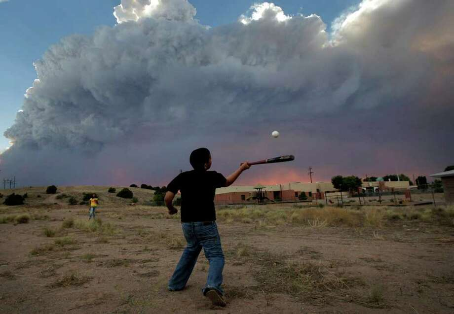 Alex Lopez, center, plays baseball with his sister Sugey while smoke generated by the Las Conchas fire covers the sky in Espanola, N.M., Wednesday, June 29, 2011. As crews fight to keep the wildfire from reaching the country's premier nuclear-weapons laboratory and the surrounding community, scientists are busy sampling the air for chemicals and radiological materials. Photo: Jae C. Hong, Associated Press / AP2011