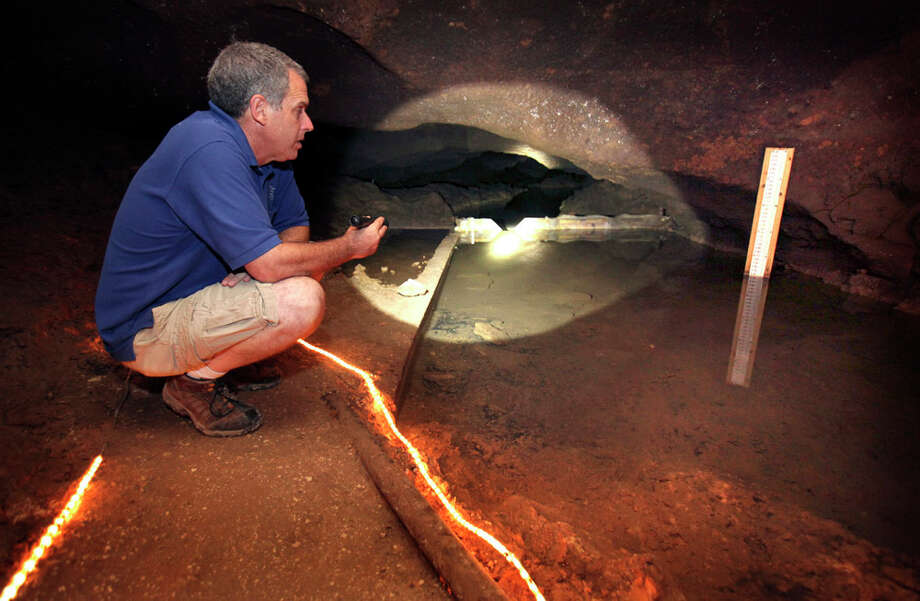 Mike Burrell, General Manager of Cave Without a Name, just outside of Boerne, checks the level of the underwater river running through the cave.  Some believe the underground river is an underground portion of the Guadalupe River. Photo: BOB OWEN / rowen@express-news.net