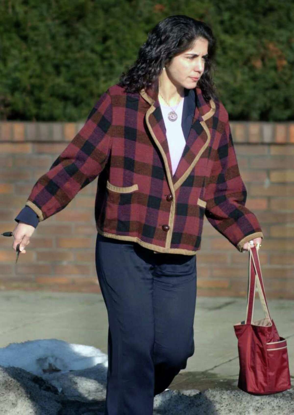 FILE - Sheila Davalloo walks to her car from the Westchester County Courthouse in 2004 after the day's proceedings in her attempted murder trial of husband Paul Christos ended. Davalloo is suspected of killing Anna-Lisa Raymundo in Stamford in 2002.
