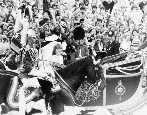 Prince Charles and Lady Diana Spencer wave to the crowd as the drive back to Buckingham Palace in London on July 29, 1981 after their wedding in St. Paul's Cathedral. (AP Photo)