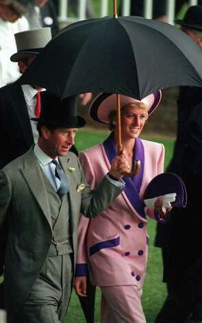 The Prince and Princess of Wales take shelter under an umbrella while attending the second day of the Royal Ascot horse race meet near London, Wednesday, June 20, 1990.   (AP Photo/Martyn Hayhow) Photo: MARTIN HAYHOW, STR