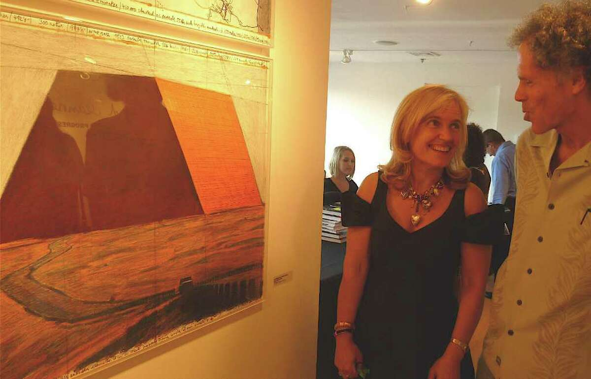 """Helen Klisser, director of visual arts for the Westport Arts Center, and artist Miggs Burroughs discuss Christo's """"Mastaba"""" project at the center Thursday night for the opening of an exhibit on Christo's next large-scale art projects."""