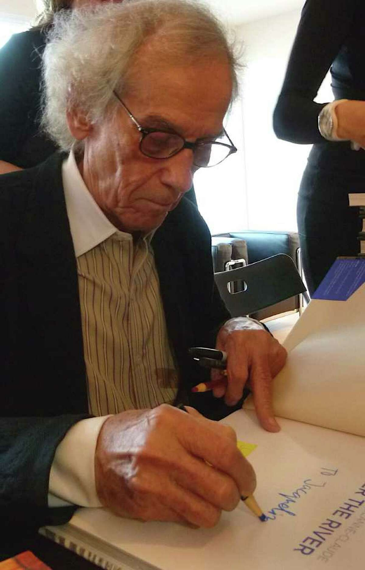 Christo signing books at the Westport Arts Center on Thursday night.
