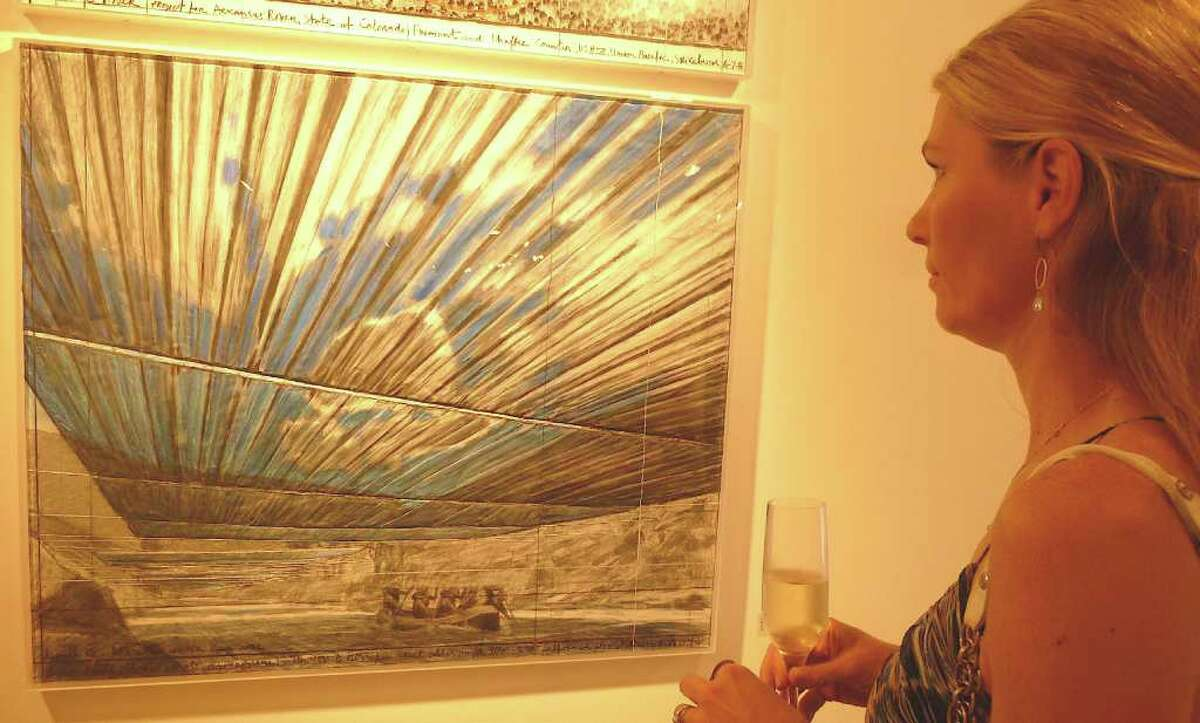 """Westport Arts Center board member Dale Najarian studies an """"Over the River"""" collage by Christo from 2008."""