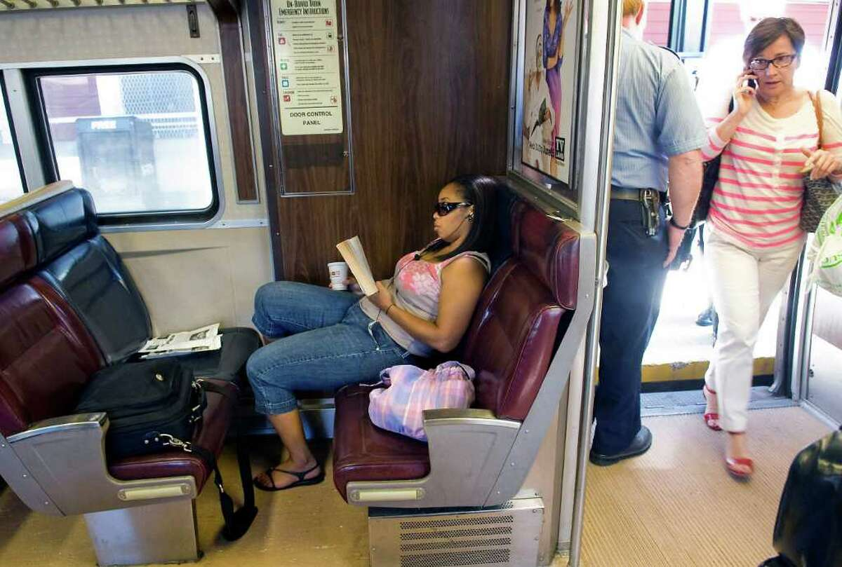 Aracelis Warren reads on the Metro-North train as passengers board while talking on cell phones en route to Grand Central Station from Greenwich, Conn. on Friday July 1, 2011. Metro-North is considering the introduction of quiet cars and is running a trial on the West of Hudson service between Pt. Jervis and Hoboken.