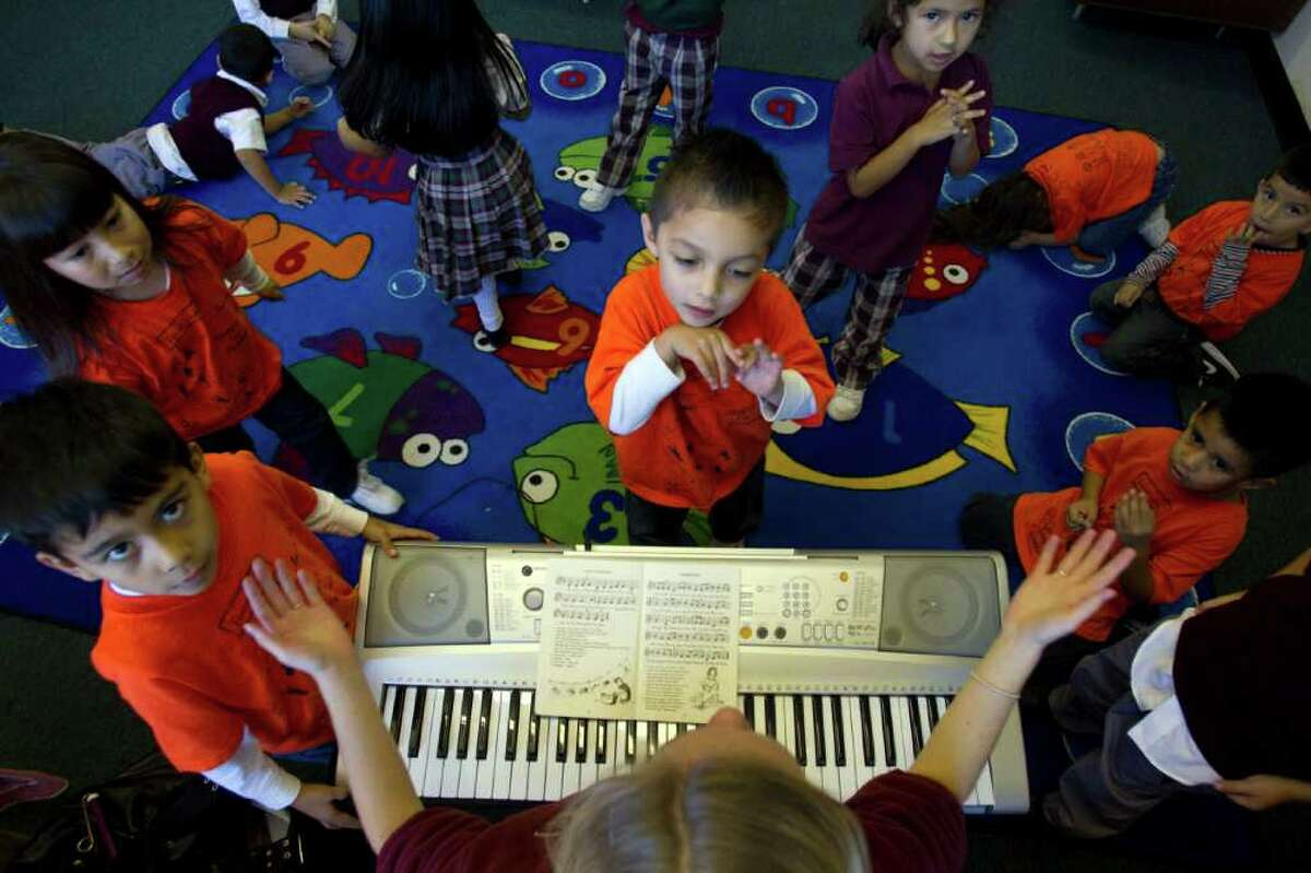 Music teacher, Maggie McGrath, leads a pre-kindergarten music class as Joaquin Montezuma, 4, (center) listens at Our Lady of Guadalupe Catholic School Friday, Nov. 19, 2010, in Houston. The Archdiocese has started a fundraising campaign to help support 13 inner-city parish schools, which educate mainly low-income minority kids and which the parish no longer can afford to support. ( Johnny Hanson / Houston Chronicle )