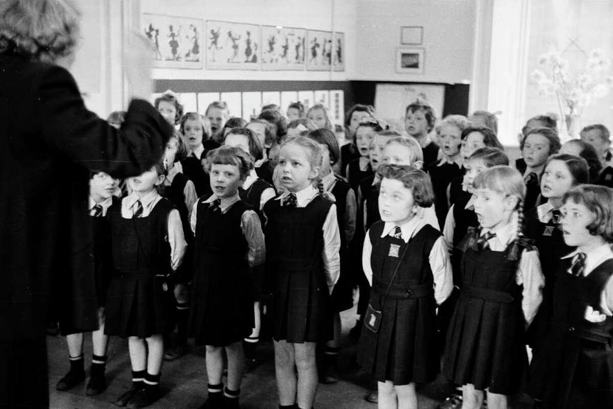 18th June 1955: A classroom of young pupils at the Glasgow High School for Girls, all singing in unison. Garnethill Public School became the Glasgow High School for Girls in 1898 and has gained an excellent reputation for producing successful graduates. Under the current headmistress, Miss Frances Barker, girls have been encouraged to take up fencing to build character and attend practical home economics lessons, such as dressmaking and cookery. The girls also study a wide range of traditional subjects and have their say in the running of the school at a weekly meeting of the teachers and prefects. Original Publication: Picture Post - 7807 - The School for Character - pub. 1955 (Photo by John Murray/Picture Post/Getty Images)