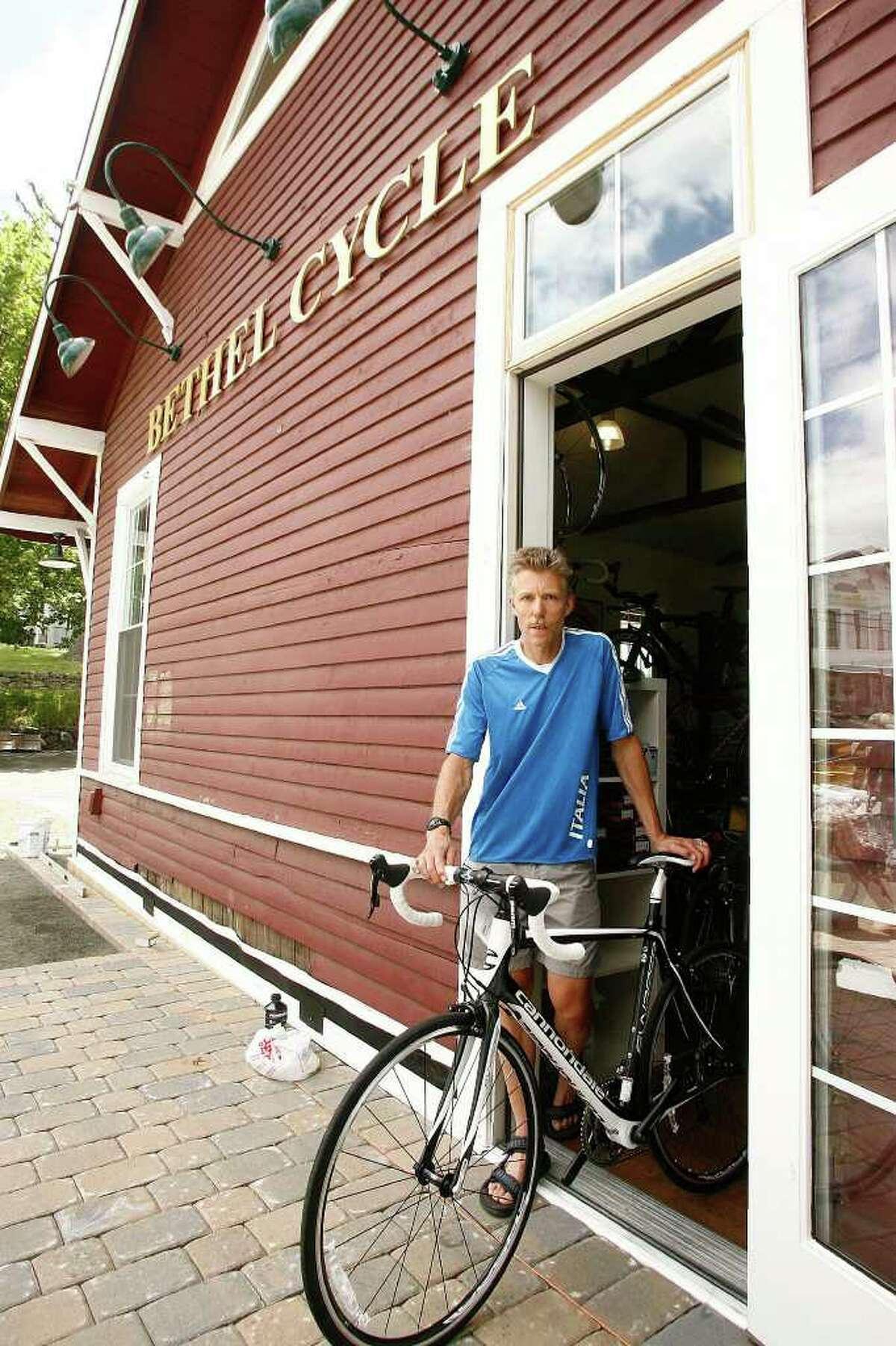 Owner and manager Greg Pelican poses for a photograph in the doorway of Bethel Cycle's new location in the historic train station in Bethel on Friday, July 1, 2011.