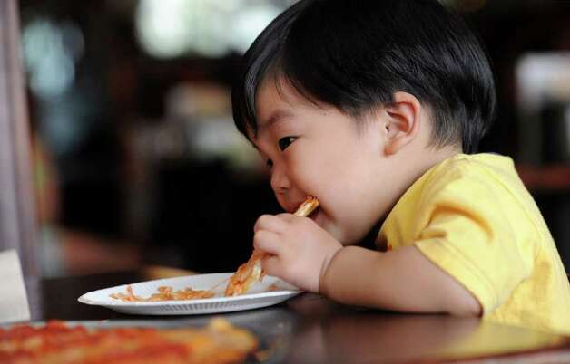 Brendan Lee, 1, takes a big bite of pizza at Colony Grill in Fairfield on Friday, July 1, 2011. Photo: Lindsay Niegelberg / Connecticut Post