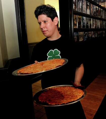 Alberto Munoz brings hot pizza pies to tables at Colony Grill in Fairfield on Friday, July 1, 2011. Photo: Lindsay Niegelberg / Connecticut Post