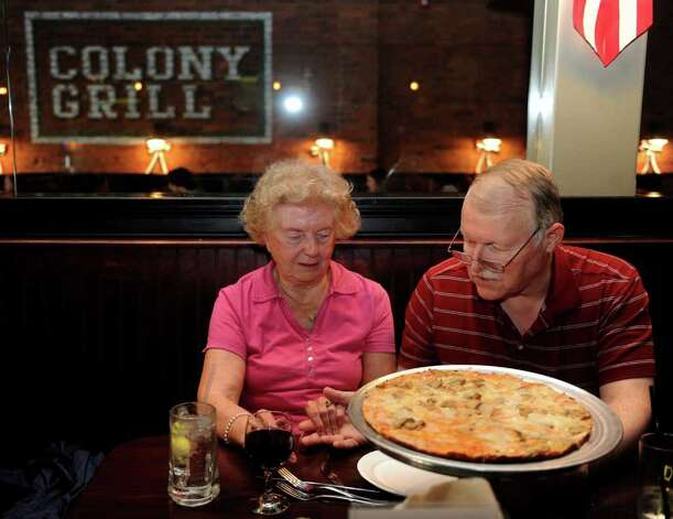 Rich and Mary Ann Kendall hold hands as they say a prayer over their pizza at Colony Grill in Fairfield on Friday, July 1, 2011. The Kendalls live in Stratford and said they drive to Fairfield for the pizza every Friday. Photo: Lindsay Niegelberg / Connecticut Post