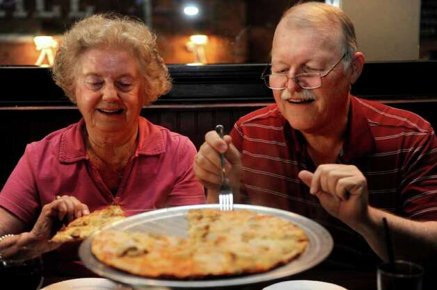 After a prayer, Rich and Mary Ann Kendall dig in to their pizza at Colony Grill in Fairfield on Friday, July 1, 2011. The Kendalls live in Stratford and said they drive to Fairfield for the pizza every Friday. Photo: Lindsay Niegelberg / Connecticut Post