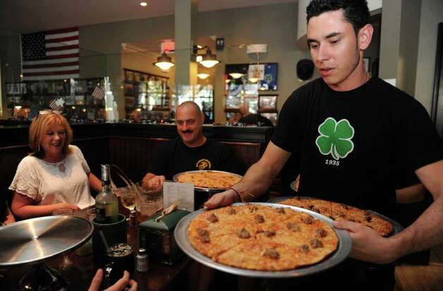 Lukas Garzon serves pizza at Colony Grill in Fairfield on Friday, July 1, 2011. Photo: Lindsay Niegelberg / Connecticut Post