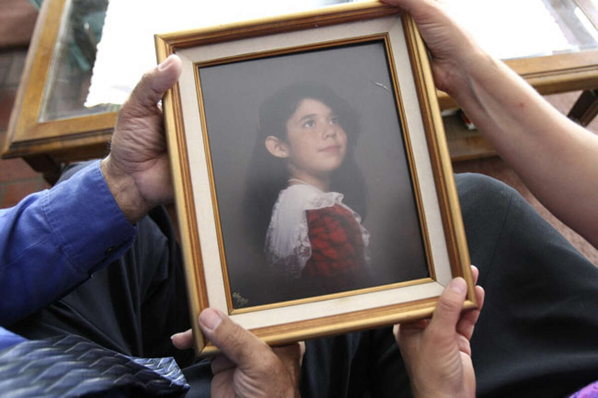 Rene and Cindy Sauceda hold a photo of Adria Sauceda who was raped and murdered in 1994.