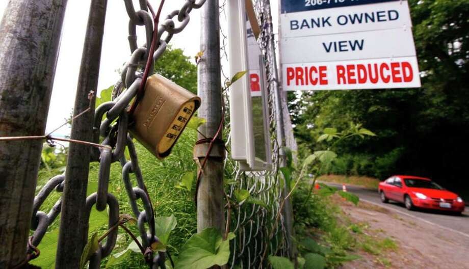 """In this June 9, 2011 photo, a """"bank-owned view  price reduced,"""" lot is chained and locked but advertised for sale, in Seattle. (AP Photo/Elaine Thompson) Photo: Elaine Thompson"""