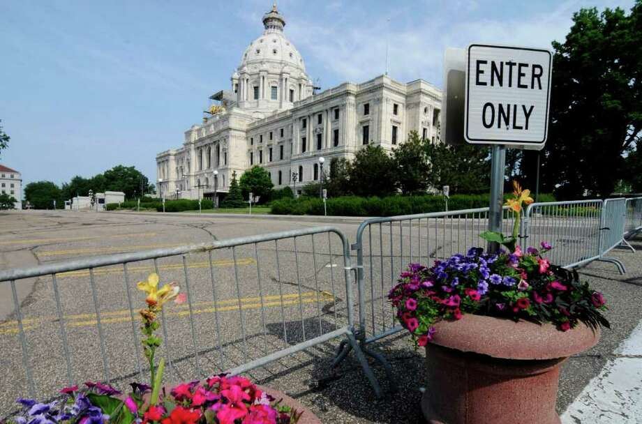 Barriers were in place on the road in front of the Minnesota State Capitol  Friday, July 1, 2011 in St. Paul, Minn., after negotiations over the state budget between Republican lawmakers and Democratic Gov. Mark Dayton broke down and the government shutdown at midnight. AP Photo/Jim Mone) Photo: Jim Mone