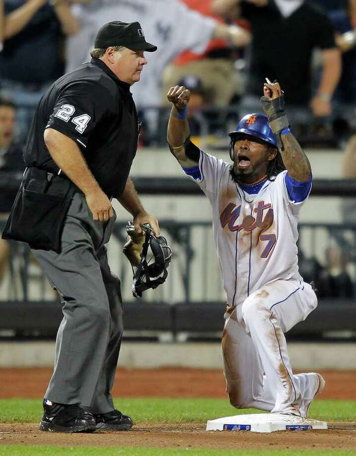New York Mets' Jose Reyes, right, reacts after umpire Jerry Lane call him out at third base as he tried to advance to third on a fly ball out hit by Justin Turner in the seventh inning of a baseball game against the New York Yankees at Citi Field in New York, Friday, July 1, 2011. (AP Photo/Paul J. Bereswill) Photo: Paul J. Bereswill