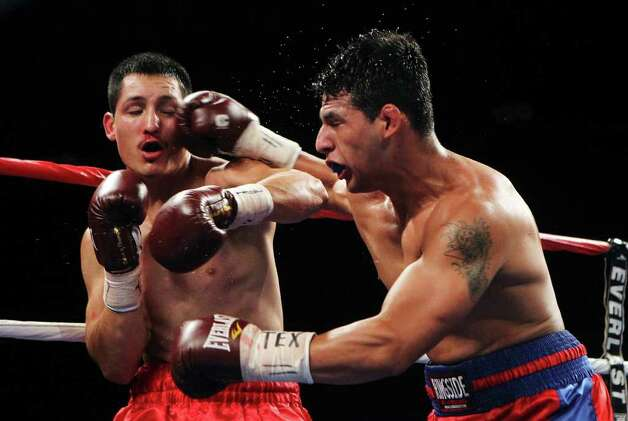 Mark Trujillo (left) of San Antonio takes a punch to the face by Randy Fuentes in a welterweight bout for ESPN Fight Night at the Freeman Coliseum on Friday, July 1, 2011. Trujillo lost the bout. Photo: Kin Man Hui/kmhui@express-news.net / San Antonio Express-News
