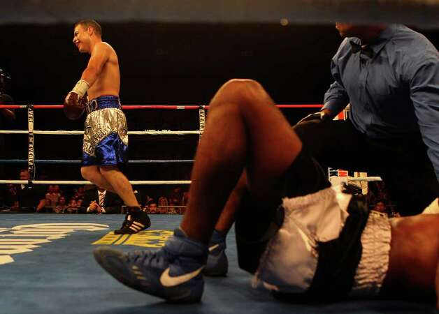 Abraham Esquivel (left) of San Antonio prances around the ring after knocking down Pedro Dominguez for a knockout 48 seconds into the first round in a lightweight bout for ESPN Fight Night at the Freeman Coliseum on Friday, July 1, 2011. Photo: Kin Man Hui/kmhui@express-news.net / San Antonio Express-News