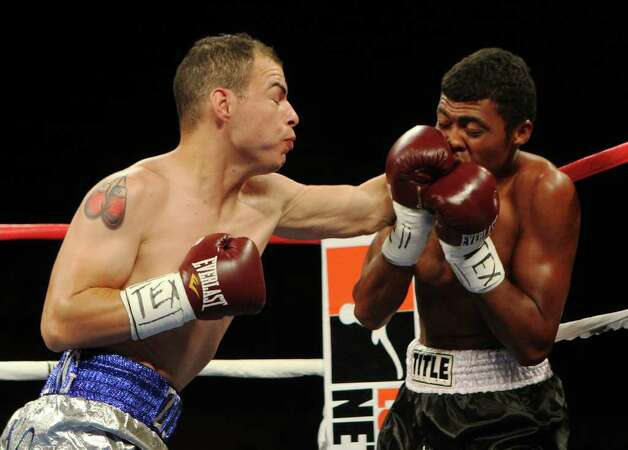 Abraham Esquivel (left) of San Antonio takes a shot on Pedro Dominguez in a lightweight bout for ESPN Fight Night at the Freeman Coliseum on Friday, July 1, 2011. Esquivel knocked out Dominguez 48 seconds into the first round. Photo: Kin Man Hui/kmhui@express-news.net / San Antonio Express-News