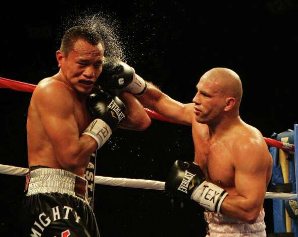 Mark Melligan (left) takes a punch to the head from Sebastian Lujan in a welterweight bout for ESPN Fight Night at the Freeman Coliseum on Friday, July 1, 2011. Lujan won on a knock out in the ninth round. Photo: Kin Man Hui/kmhui@express-news.net / San Antonio Express-News