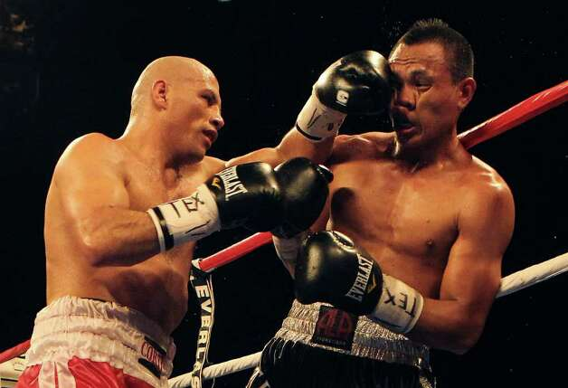 Sebastian Lujan (left) lands a punch against Mark Melligan in a welterweight bout for ESPN Fight Night at the Freeman Coliseum on Friday, July 1, 2011. Lujan won on a knock out in the ninth round. Photo: Kin Man Hui/kmhui@express-news.net / San Antonio Express-News