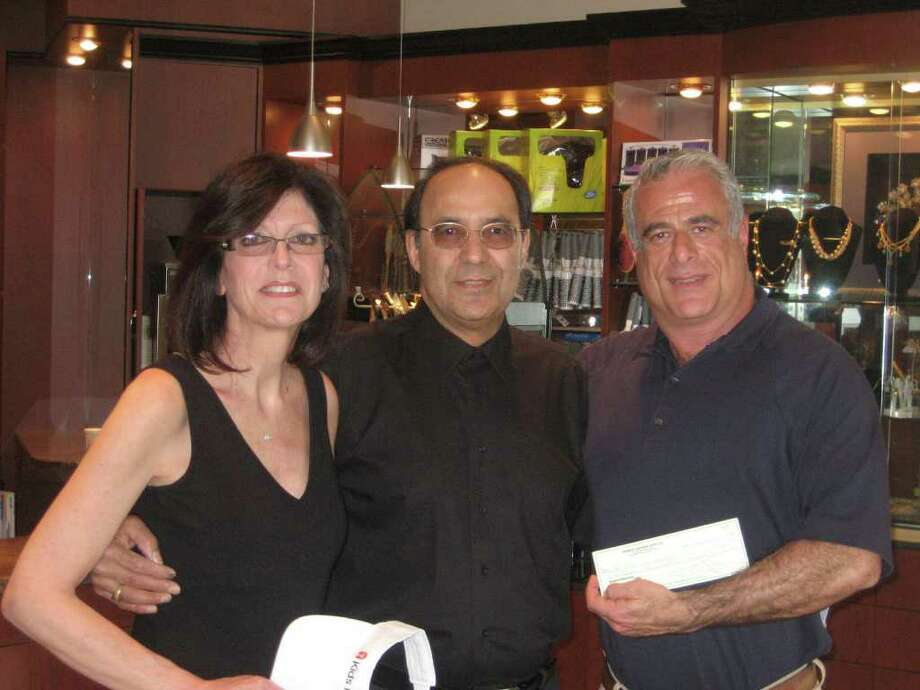 Kids in Crisis recently received a donation of $1,600 from Leon and Cathy Vizzari, owners of Visible Changes Salon and Academy in Old Greenwich. The Vizzaris donated $1 to Kids in Crisis for every client seen in April, which was National Child Abuse Prevention Month. Alon Marom, right, director of Corporate and Community Giving at Kids in Crisis, is pictured receiving the donation from the Vizzaris. Photo: Contributed Photo