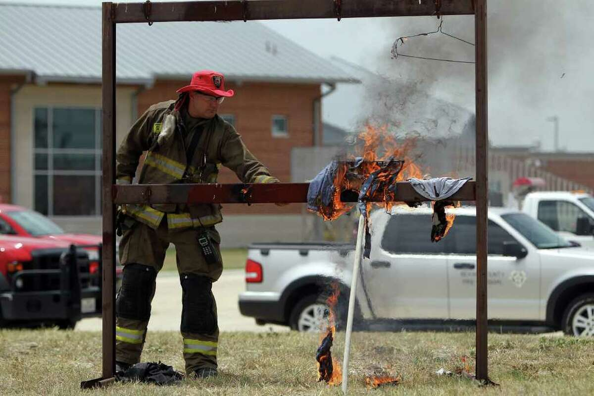Firefighter Scott McCreless exposes loose clothing to a lit sparkler to show how quickly it can go up in flames during a demonstration about the dangers of fireworks with the extreme draught conditions this year at the San Antonio Fire Department Training Academy, Friday, July 1, 2011. (Jennifer Whitney/ Special to the San Antonio Express-News)