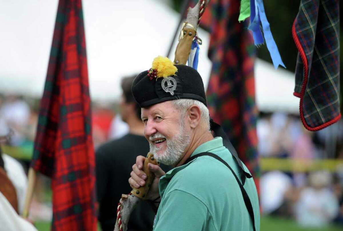 Rick Mattice, of Stamford, standing with clan Malcolm, looks back as the pipe bands march onto center field during opening ceremonies of the 88th Annual Round Hill Highland Games at Cranbury Park in Norwalk, Conn. Saturday, July 2, 2011.