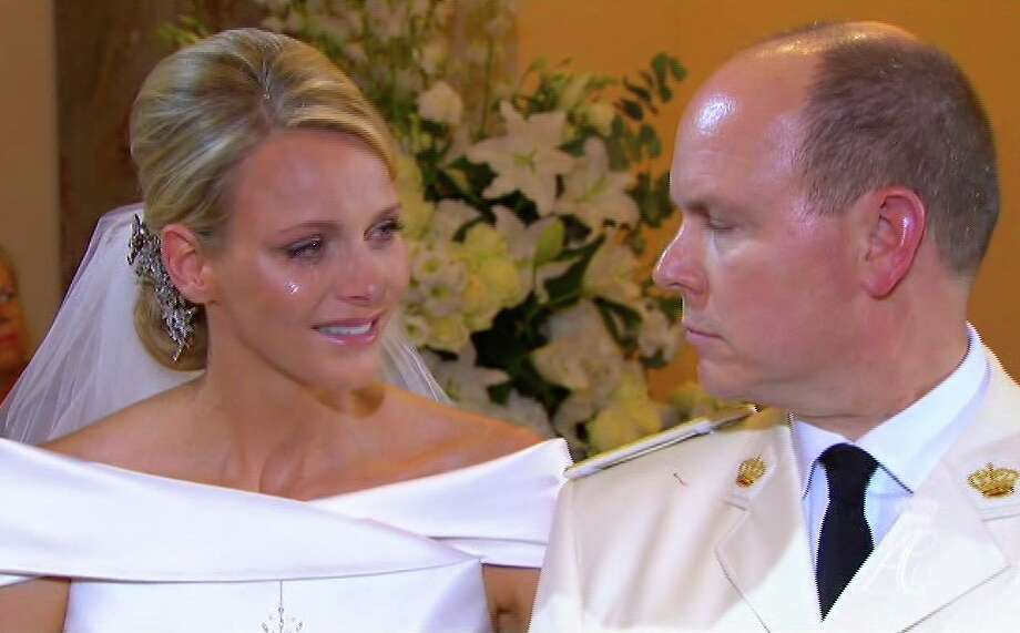 This image taken from the pool television service via Associated Press Television News shows Prince Albert II of Monaco, right, as he speaks to his new bride, Charlene Princess of Monaco with a tear on her cheek during their wedding service in the chapel of the Sainte Devote Church Saturday, July 2, 2011. (AP Photo/Television Pool via APTN)  NO ARCHIVE  PHOTO MAY NOT BE USED FOR MORE THAN 14 DAYS FROM SATURDAY Photo: Anonymous, ASSOCIATED PRESS / AP2011
