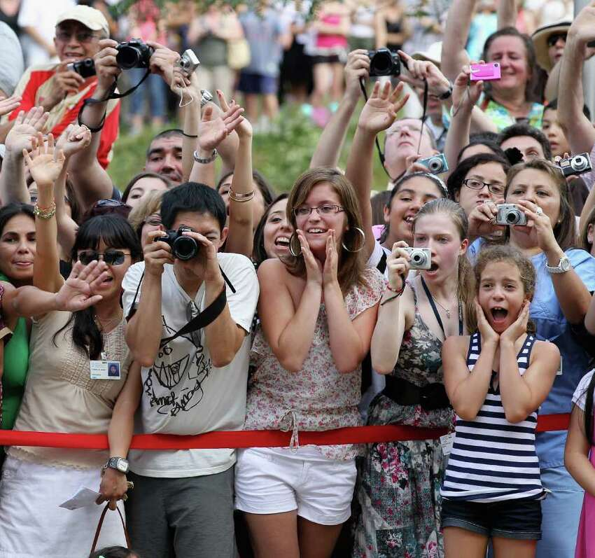 Royal fans try to catch a glimpse of Prince William, Duke of Cambridge and Catherine, Duchess of Cambridge as they visit Sainte-Justine University Hospital in Montreal on Saturday, July 2, 2011.  The newly married royal couple were on the third day of their first joint overseas tour. The 12-day visit to North America will take in some of the more remote areas of Canada, such as Prince Edward Island, Yellowknife and Calgary.