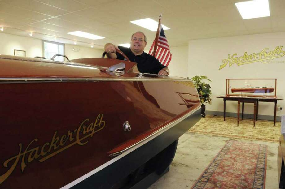 George Badcock, president and CEO of the Hacker Boat Company, sits in one of the company's racers in the showroom  on Monday, June 27, 2011 in Silver Bay.  Hacker Boat Company is the leading American manufacturer of handcrafted mahogany boats. (Paul Buckowski / Times Union) Photo: Paul Buckowski  / 00013695A
