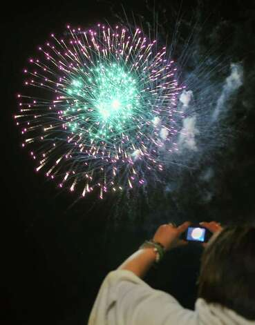 A fireworks fan uses a cell phone to photograph during the annual Steamboat Meet and Fourth of July Celebration at the Waterford Visitor Center Saturday July 2, 2011. Photo: John Carl D'Annibale, John Carl D'Annibale / Times Union / 00013776A
