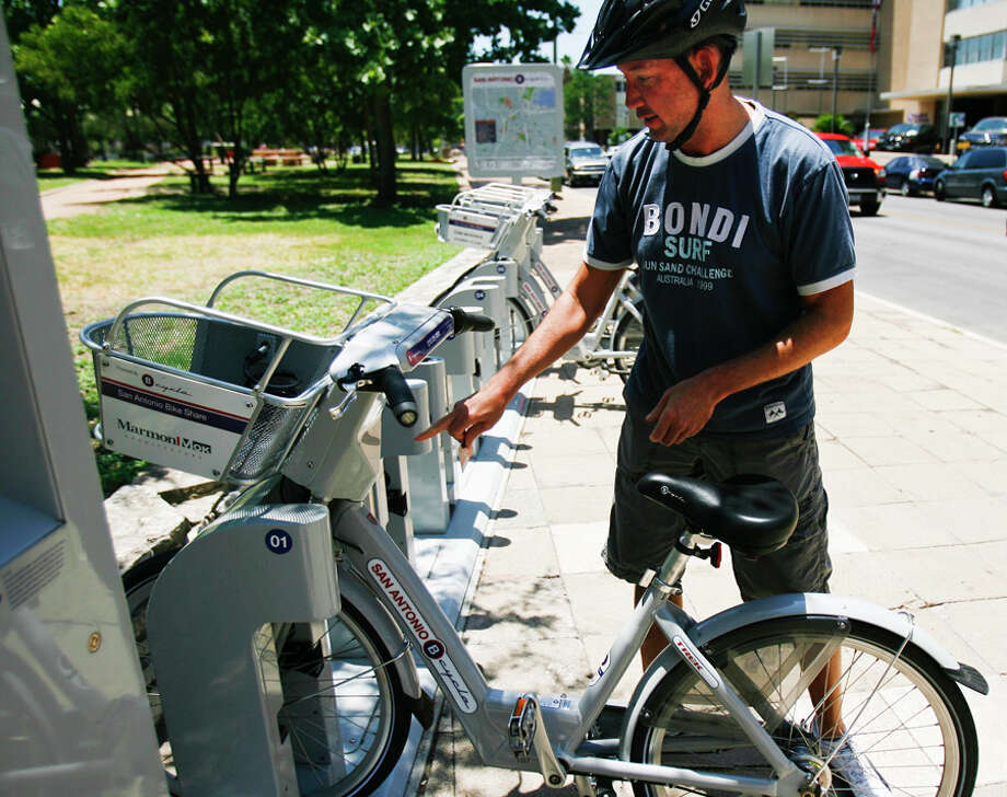 Robert Young unlocks a bike from the B-cycle sharing system. Young is one of the top users in the program. Photo: Sally Finneran/sfinneran@express-news.net